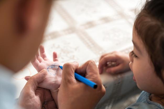 Close-up van kind en ouders met marker