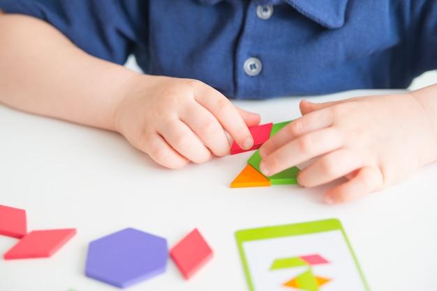Close up van kind handen spelen heldere houten tangram speelgoed. creatieve baby maakt nieuwe vormen.