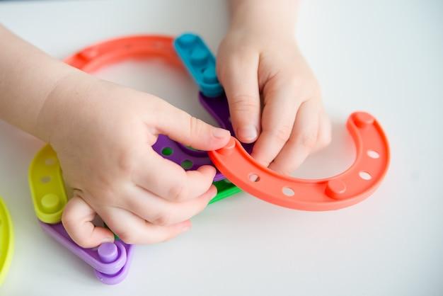 Close-up van kind handen spelen heldere plastic speelgoed constructeur. creatieve baby maakt nieuwe vormen. kopieer ruimte