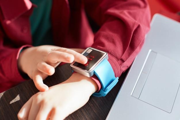 Close-up van kind` s handen met slim horloge. wat betreft elektronisch horloge. draagbaar gadgetconcept. tijd weergeven. smartwatch gebruiken terwijl u in de buurt van de laptop zit. technologie en mensen concept.