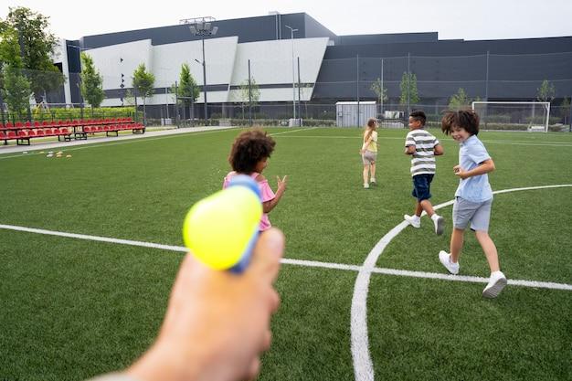 Close-up van kinderen die buiten met een waterpistool spelen