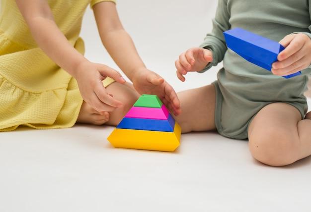 Close-up van kinderen die met een kleurrijke piramide op een witte achtergrond spelen