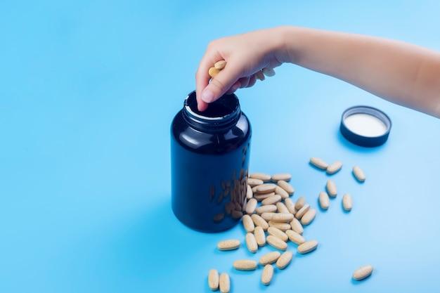 Close-up van kinderhanden met pillen, jong kind spelen alleen met pillen tabletten thuis. buiten bereik van kinderen houden. geen medicijnkastje, bewust maken.