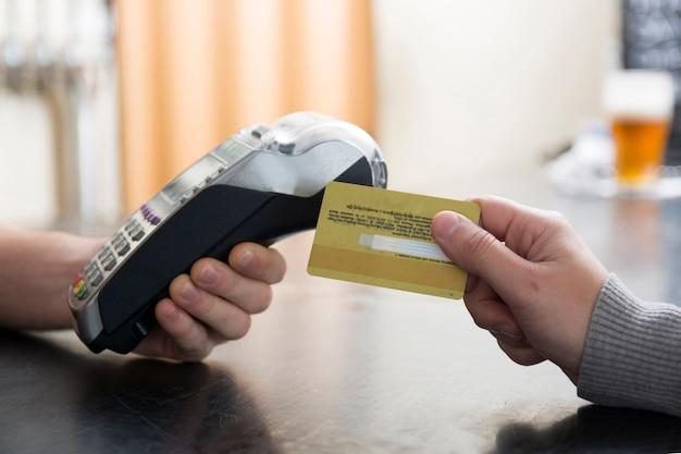 Close-up van klant die door creditcard betaalt