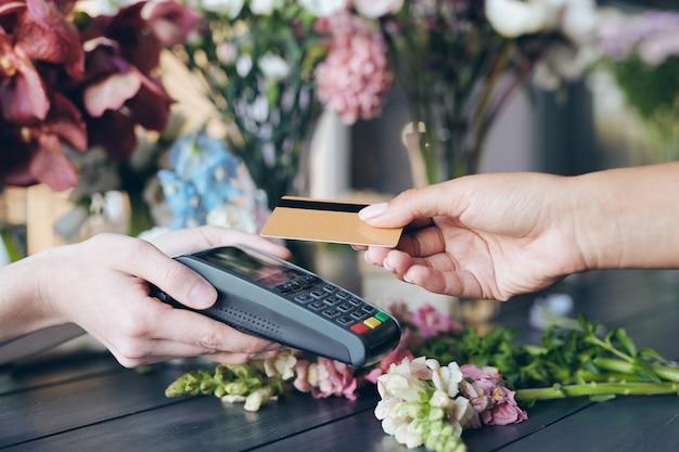 Close-up van klant draadloze kaart aan terminal zetten terwijl het betalen voor bloemen in bloemenwinkel, exemplaarruimte