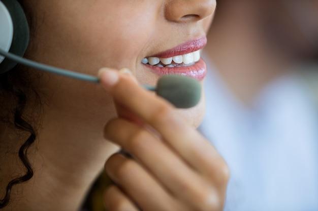 Close-up van klantenservicestafmedewerker die haar mic aanpast