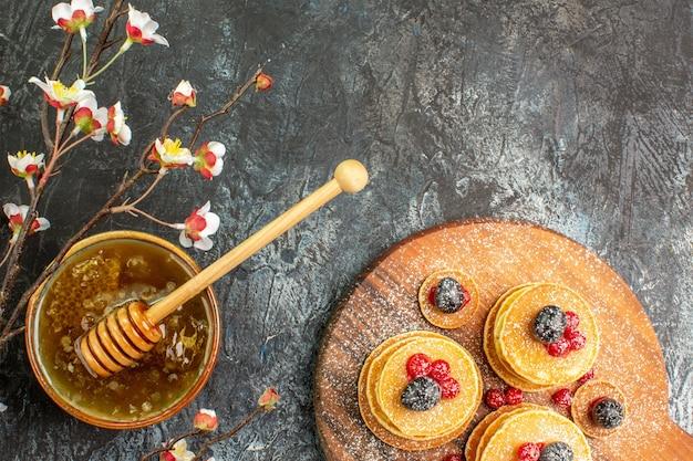 Close-up van klassieke amerikaanse pannenkoeken honing in een kom op grijs