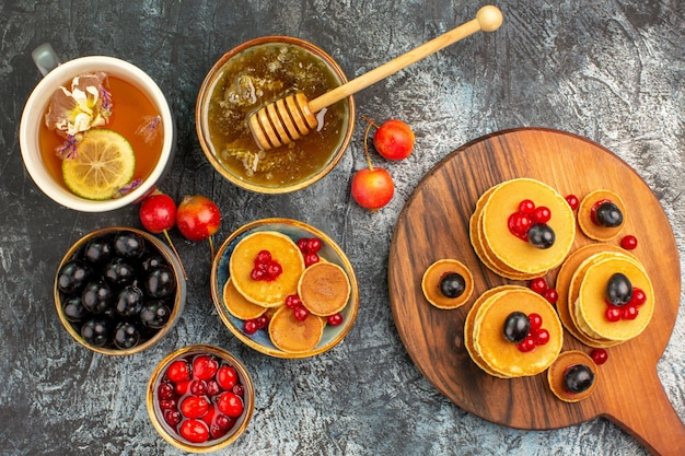 Close-up van klassieke pannenkoeken op snijplank met honing en fruit