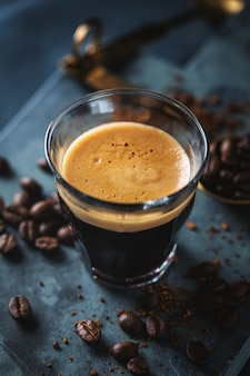 Close-up van klassieke verse espresso geserveerd op donkere ondergrond.