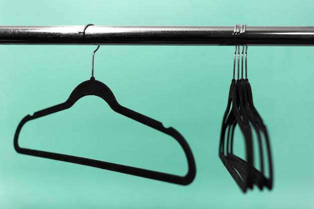 Close-up van kledingrek met zwarte lege hangers op oppervlak van aqua menthe-kleur.