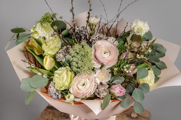 Close-up van klein roze bloemenboeket in glasvaas met vage grijze achtergrond. bruiloft of verjaardag, valentijnsdag concept.