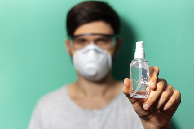 Close-up van kleine fles ontsmettingsgel in mannenhand met medische gezichtsmasker en veiligheidsbril bril op oppervlak van aqua menthe kleur.