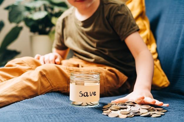 Close up van kleine kind jongen jongen handen grijpen en stapel munten in glazen pot met save