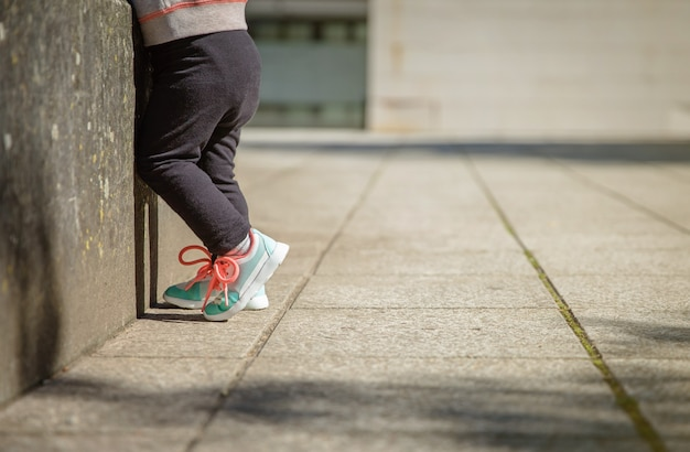 Close-up van kleine meisjesbenen met sneakers en zwarte leggins die buitenshuis trainen