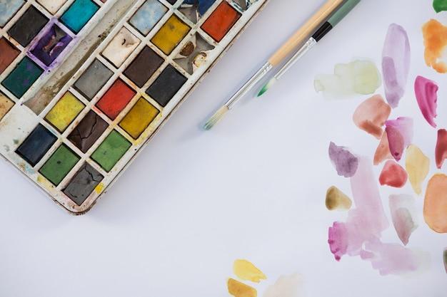 Close-up van kleurrijk palet, verfborstels en papier
