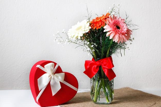 Close-up van kleurrijke bloemen in de pot op het rustieke servet en een hartvormige doos met witte achtergrond. san valentijnsdag concept