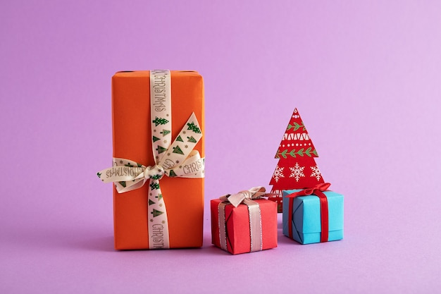 Close-up van kleurrijke geschenkdozen en een papieren kerstboom op de paarse achtergrond
