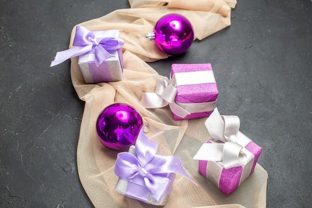 Close-up van kleurrijke geschenken decoratie accessoires voor het nieuwe jaar op naakt kleur handdoek op zwarte achtergrond