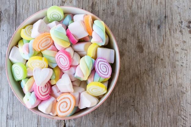 Close-up van kleurrijke miniheemst met suikergoed in kom op houten lijstachtergrond of textuur.