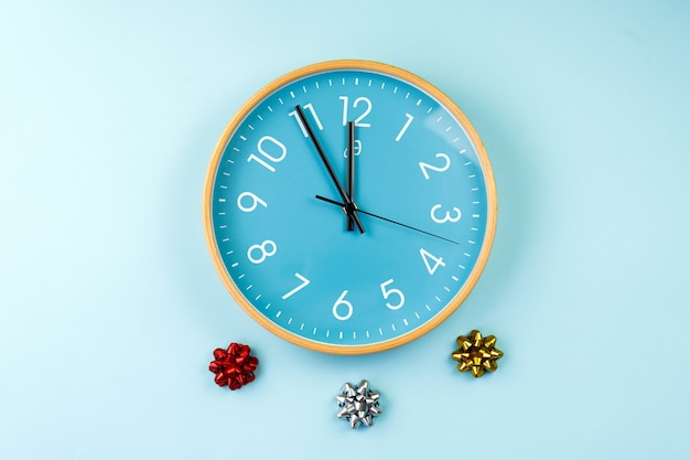 Close-up van kleurrijke muurklok op blauwe achtergrond. minimalistisch plat lag beeld van kunststof wandklok voor kerstmis.