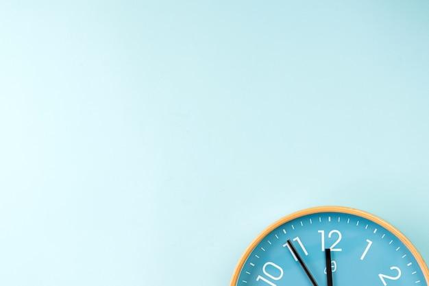 Close-up van kleurrijke muurklok op blauwe achtergrond. minimalistisch plat lag beeld van plastic wandklok.