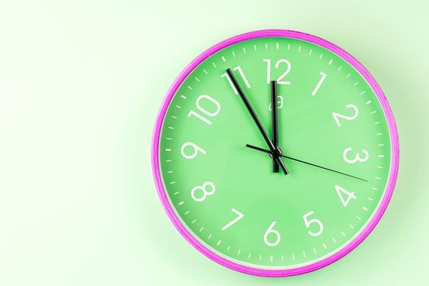 Close-up van kleurrijke muurklok op groene achtergrond. minimalistisch plat lag beeld van plastic wandklok.