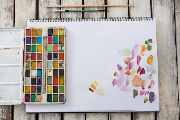 Close-up van kleurrijke paletpenselen en papier op houten oppervlak
