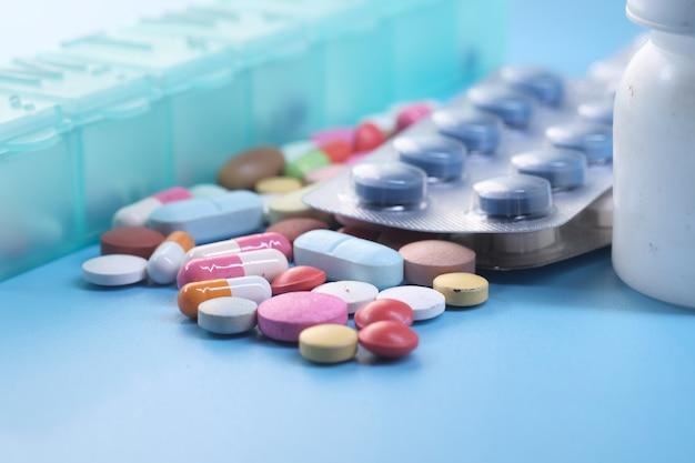 Close up van kleurrijke pillen en capsule op blauwe ondergrond.