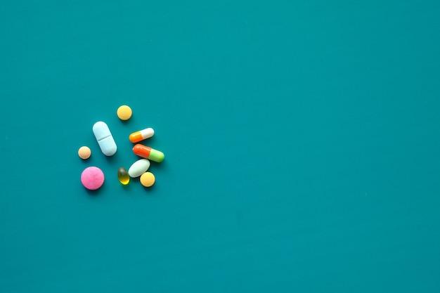 Close-up van kleurrijke pillen morsen op groene achtergrond.