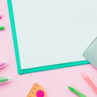 Close-up van kleurrijke potlood en witboek op roze oppervlak