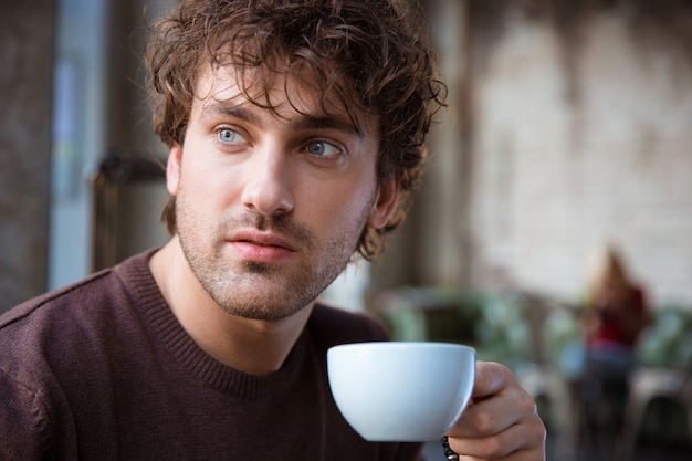 Close-up van knappe aantrekkelijke doordachte contemplatieve krullende man koffie drinken drinking