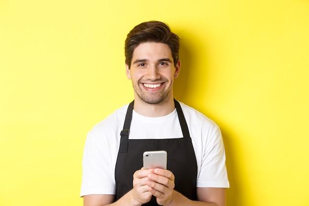 Close-up van knappe barista die bericht op mobiele telefoon verzendt, gelukkig glimlacht, staande over gele achtergrond