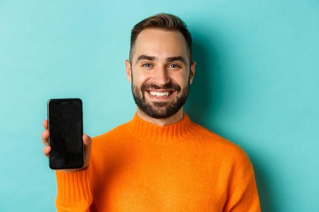 Close-up van knappe bebaarde man in oranje trui met smartphonescherm en glimlachend met prom...