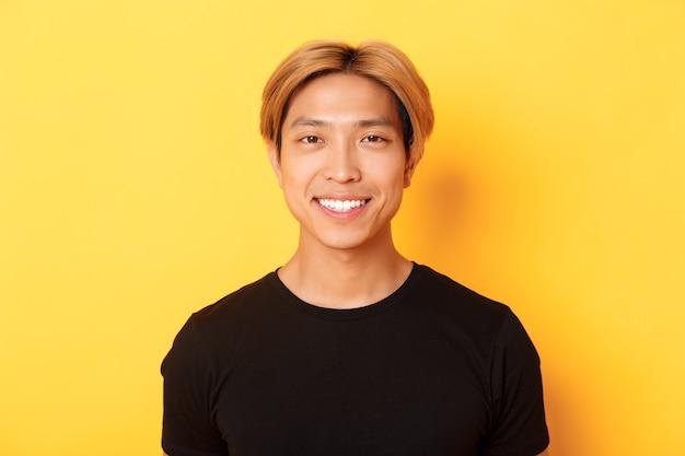 Close-up van knappe blonde aziatische man in zwart t-shirt, glimlachend gelukkig, staande over gele muur.