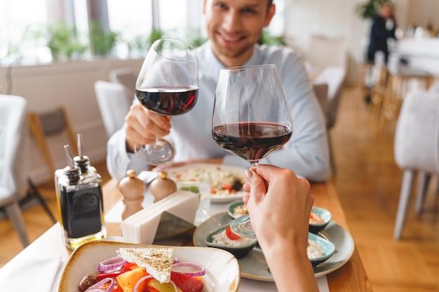 Close up van knappe heer en dame rammelende glazen alcoholische drank in café