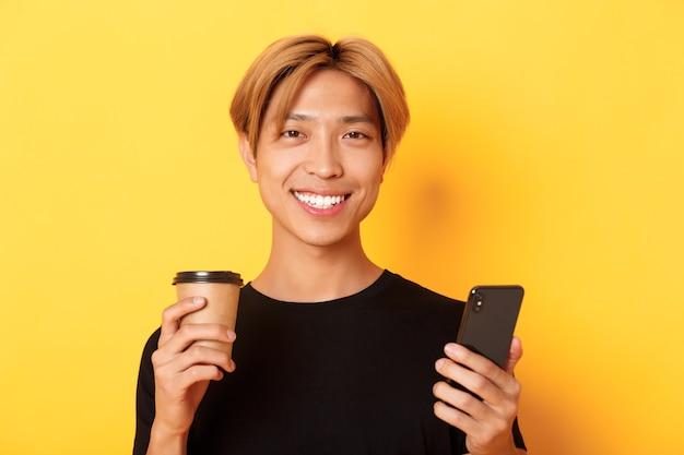 Close-up van knappe jonge aziatische kerel die gelukkig glimlacht, smartphone gebruikt en afhaalkoffie drinkt, die zich over gele muur bevindt