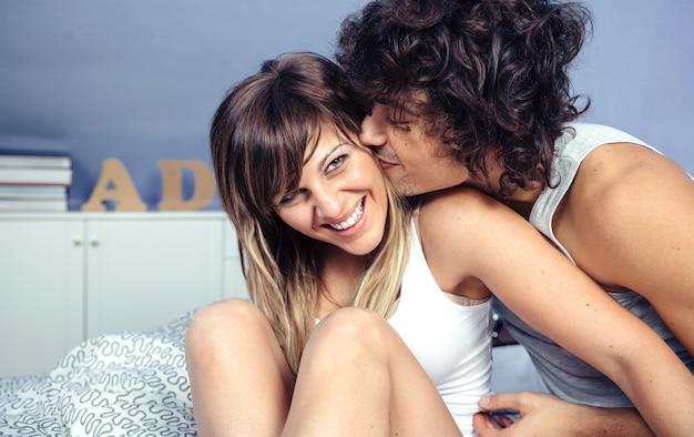 Close-up van knappe jonge man die zoent en kriebelt met mooie vrouw die lacht boven een bed. liefde en paar relaties concept.