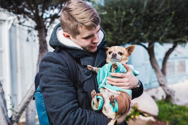 Close-up van knappe jonge man met een schattige chihuahua hond buiten.