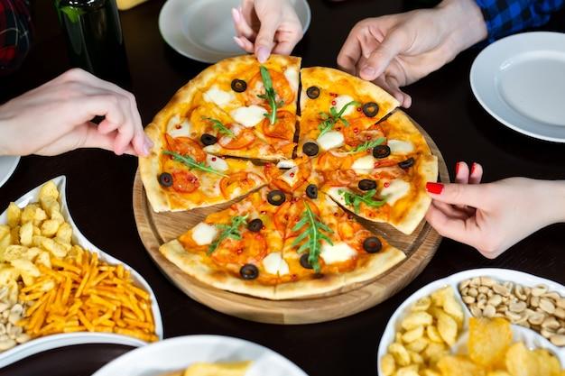 Close-up van knappe jonge vrienden drinkt bier en pizza eten in pub