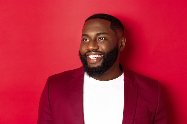 Close-up van knappe man met baard, kijkend naar links en glimlachend vrolijk, staande op rode achtergrond.