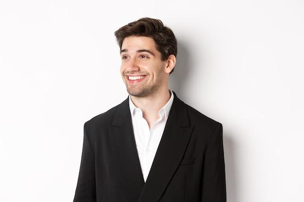 Close-up van knappe mannelijke ondernemer in pak, naar links kijkend en glimlachen, staande tegen een witte achtergrond.