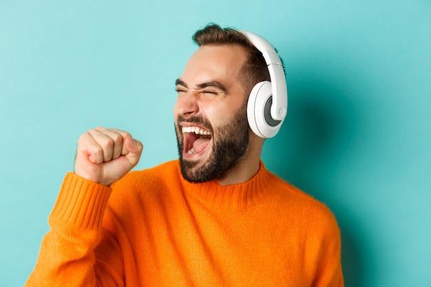 Close-up van knappe moderne man luisteren muziek in koptelefoon, staande in oranje trui