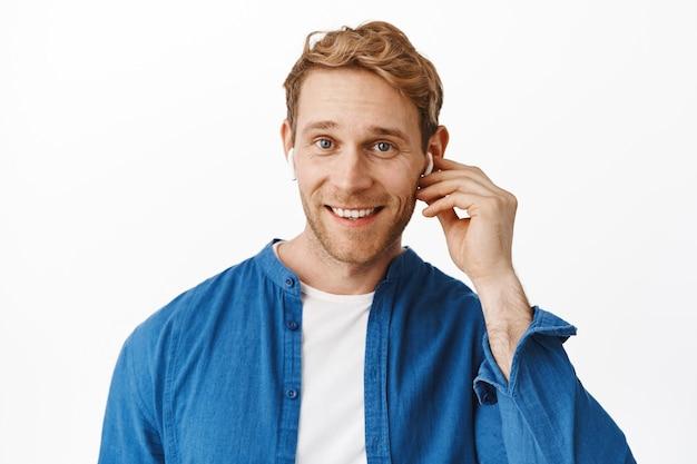 Close-up van knappe roodharige man draagt draadloze oortelefoon en glimlacht naar voren, praat met iemand in koptelefoon, luistert muziek in oordopjes, staat over witte muur