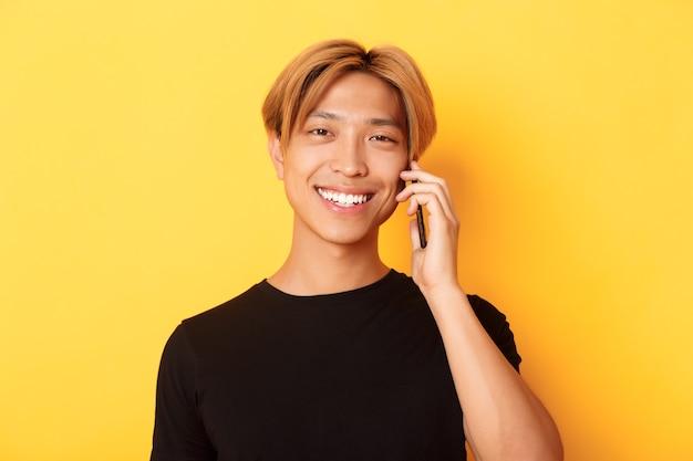 Close-up van knappe stijlvolle koreaanse man glimlachend en praten op mobiele telefoon, staande over gele muur