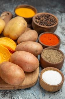 Close-up van knapperige chips en ongekookte aardappelen op houten snijplank en verschillende kruiden op grijze tafel