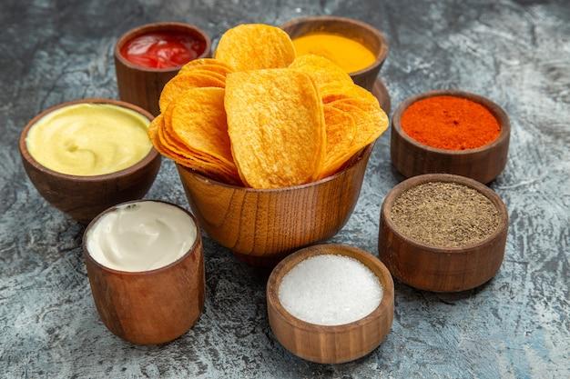 Close-up van knapperige chips op houten snijplank en verschillende kruiden op grijze tafel