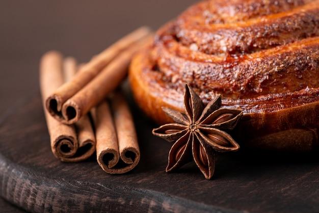 Close-up van knapperige kaneelbroodjes met anijsster kaneelstokjes op bruine snijplank