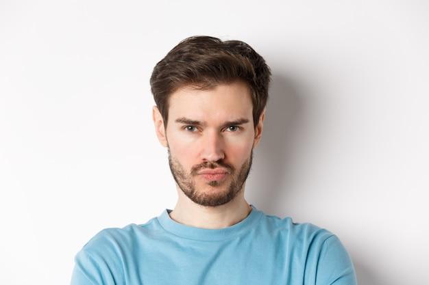 Close-up van knorrige jonge man grimassen, mokkend en beledigd gezicht maken, staande boos op witte achtergrond.