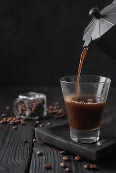 Close-up van koffie in glas wordt gegoten dat