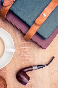 Close-up van koffie met dagboeken en rookpijp op tafel